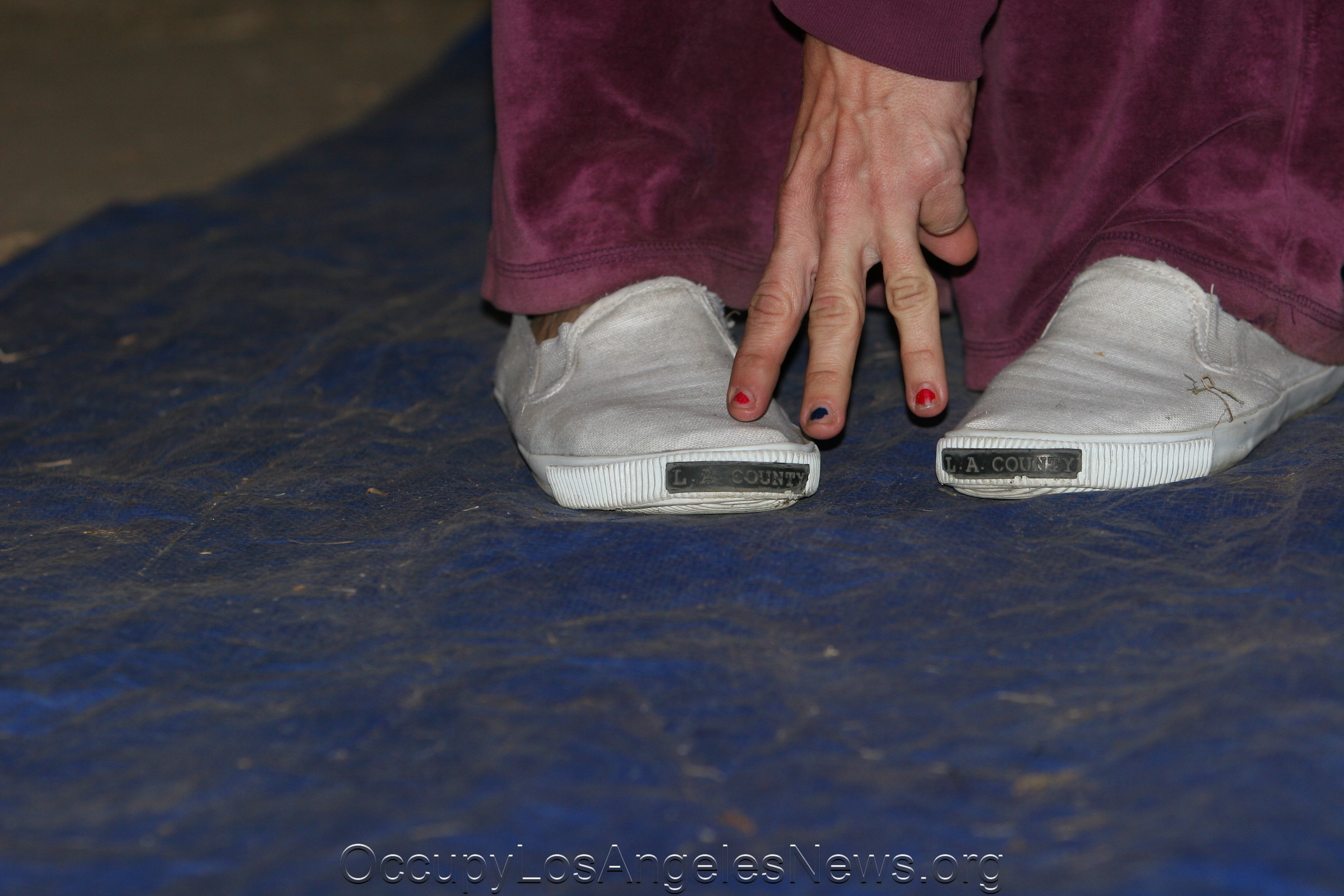 Melissa Balin showing the Los Angeles County Jail sneakers issued to her during one of her arrests while participating in Occupy Wall Street protests in Los Angeles.